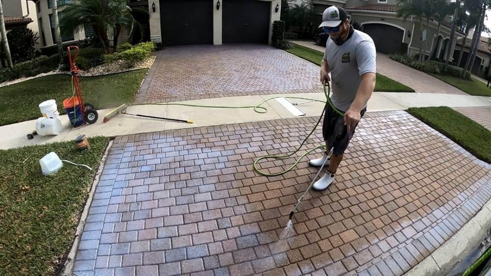 An Oleyn's service professional washing and sealing pavers on a brick driveway